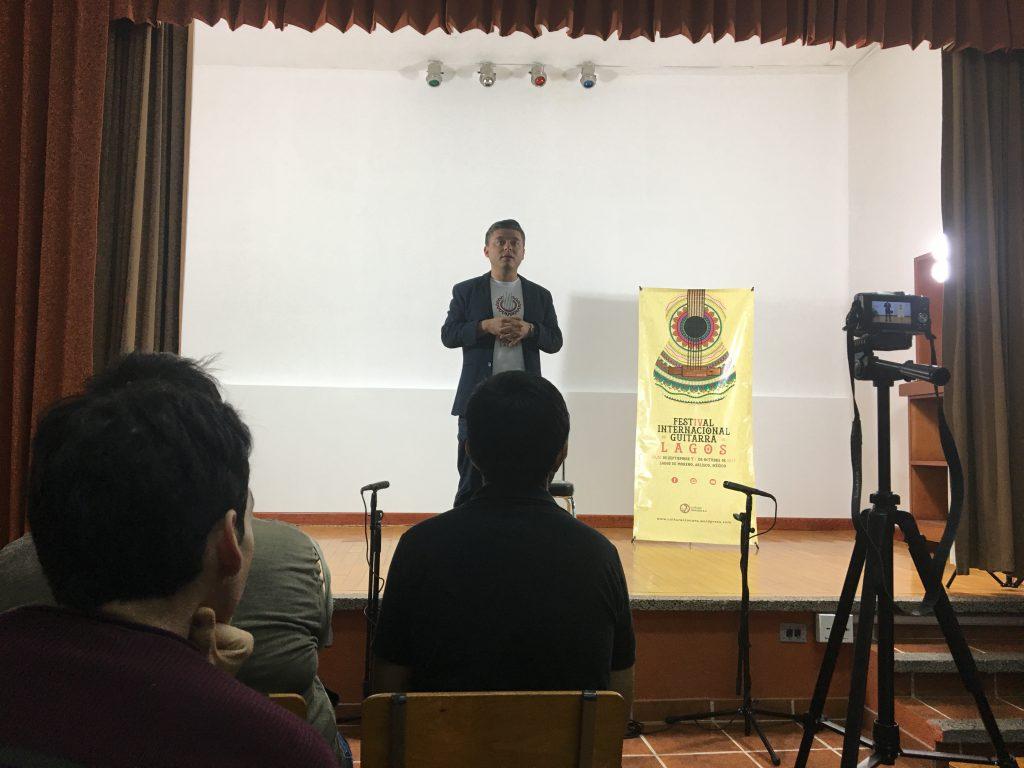 Hugo Acosta sobre un escenario, dirigiéndose a la audiencia.
